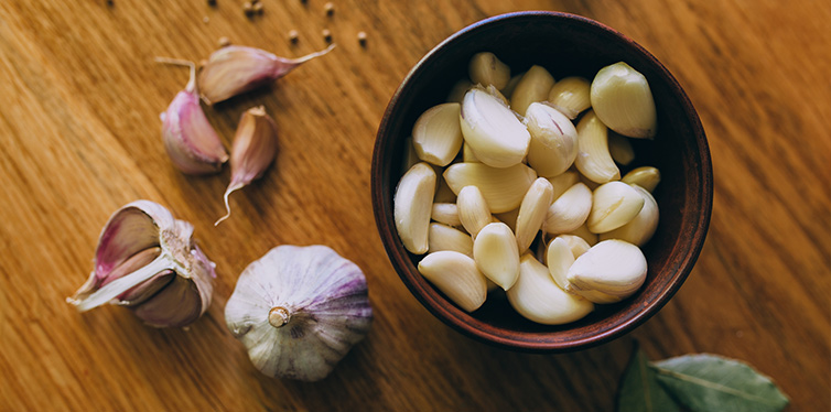 Bowl of garlic on wooden table