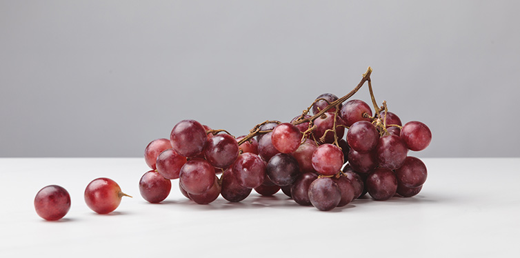pile of red grapes on gray