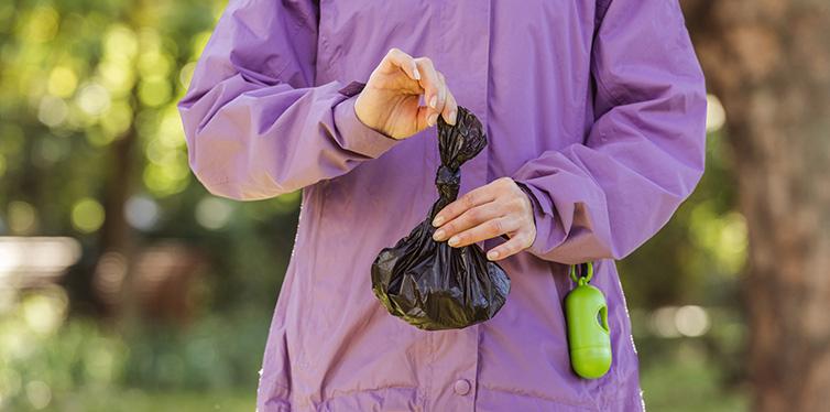 young woman holding trash bag