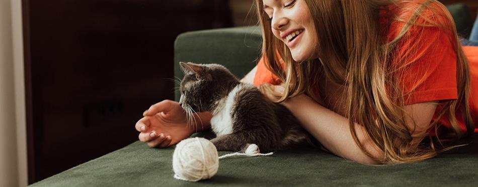 Cheerful girl playing cute cat near ball