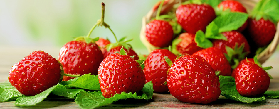 Ripe strawberries with leaves in wicker basket on wooden table on blurred background