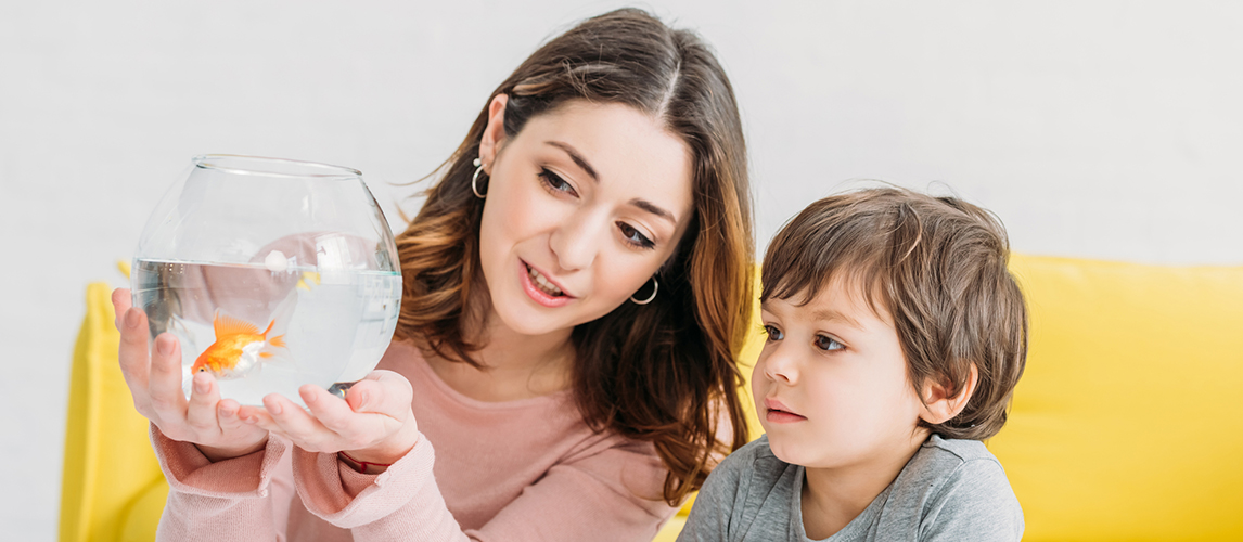 Pretty woman holding fish bowl with bright gold fish near adorable son