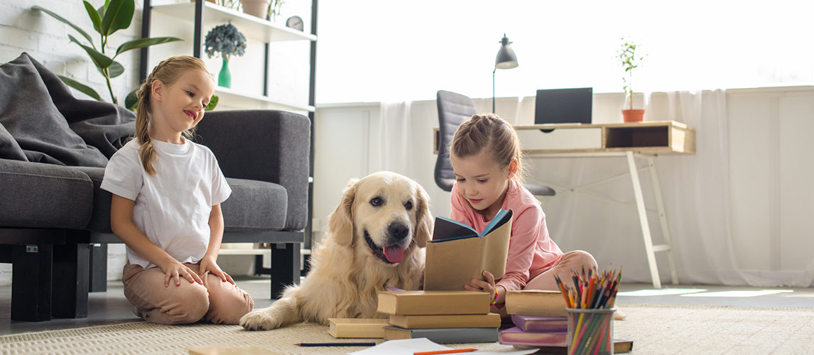 Little sisters reading books with golden retriever dog