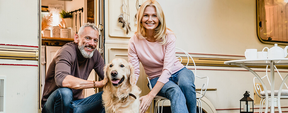 Full length portrait of aged nice-looking caucasian couple spending their free time with dog in the camper van