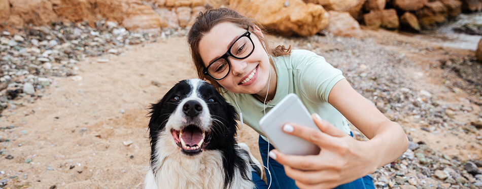 Smiling young cheerful girl in eyeglasses having fun with her dog at the beach and taking selfie with smartphone